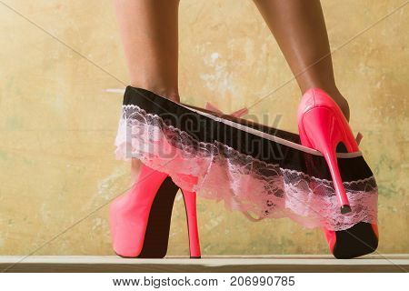 Erotic lingerie and pink high heel shoes for a seductive young woman