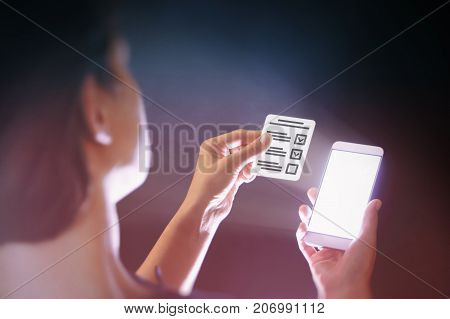 Image of a woman with a smartphone in her hand. She holds a questionnaire. Modern methods of questioning voting examining testing etc.