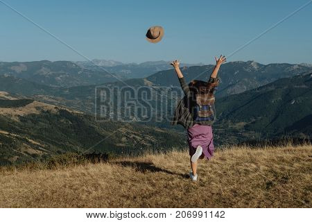 Rinning Young Woman Traveler Tosses A Hat Against The Background Of The Mountains.  Freedom Concept