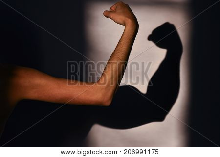 Men's muscles reality and expectation. Sports and training in the gym. Man's hand and a shadow on the wall. Expectation vs reality