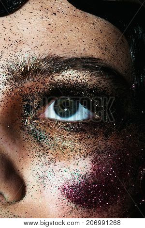 Look up white girl model with creative make-up a lot of shine for the show fashion show. Dark green eyes of young woman