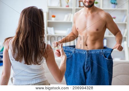 Man in oversized pants in weight loss concept with girlfriend wi