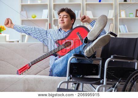 Disabled man playing guitar at home