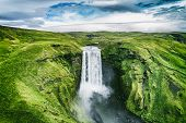 Iceland waterfall Skogafoss in Icelandic nature landscape. Famous tourist attractions and landmarks destination in Icelandic nature landscape on South Iceland. Aerial drone view of top waterfall. poster