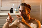 Sex and erotica concept. Guy in bathroom covered with foam with toiletries on background. Macho sitting naked in bathtub selective focus. Man with beard and involved face pointing fingers. poster