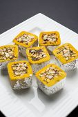 stock photo of sweet Mawa burfi for diwal wrapped with silver foili, selective focus poster