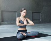 Attractive girl practicing yoga sitting in padmasana. Young woman in lotus pose, namaste with closed eyes on mat at sport club interior, copy space poster