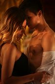 Couple dancing and kissing indoor. Romantic evening interior for loving couple. Loving people undress in intim interior. A lot of pictures in room. Wedding night. poster