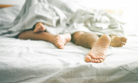 Close up of male and female feet on a bed - Loving couple having sex under under white blanket in the bedroom - Concept of sensual and intimate moment of lovers - Vintage filter - Focus on male foot