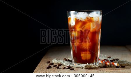 Ice Coffee In A Tall Glass With Cream Poured Over, Ice Cubes And Beans On A Old Rustic Wooden Table.