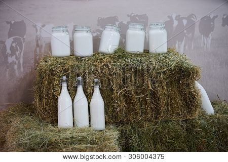 Glass Bottles With Fresh Cow Milk In A Hay, Close-up. Agriculture Industry