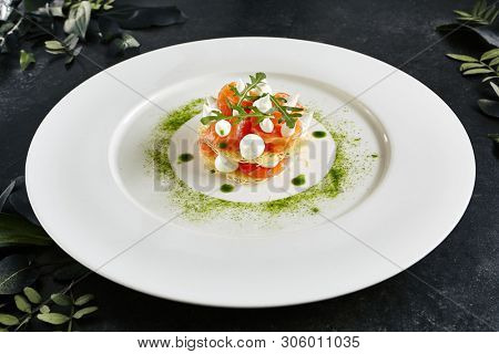 Beautiful Serving Italian Cuisine Dish of Salmon Millefeuille with Cream Cheese Mousse, Arugula and Capers. Exquisite Trout Sashimi of Sliced Red Fish on Natural Dark Stone Background poster