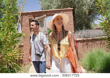 Cheerful stylish couple exploring Morocan villa and gardens poster
