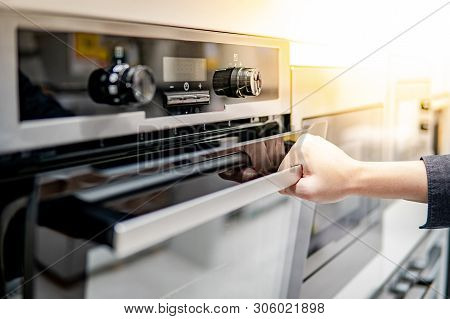 poster of Male hand opening oven door in the kitchen showroom. Buying cooking appliance for domestic kitchen. Home improvement concept