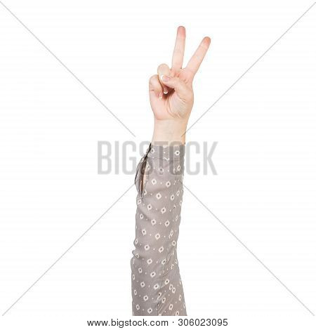 Woman Hand In Grey Blouse Showing Victory Gesture. Winning And Triumph Sign. Human Hand Gesturing Si