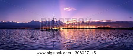 An Tranquil Pastel Mauve Coloured Nautical Waterscape Sunset Panorama In A Blue Sky Reflected In Smo