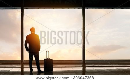 Man Standing And Looking Out At The Airport Window While Waiting For Flight Departure
