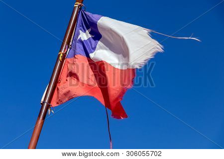 Torn Chilean Flag Flying Over The Blue Sky