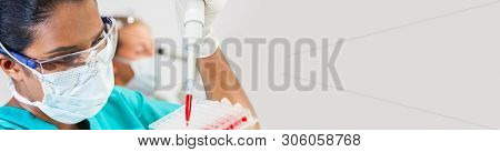 Panoramic web banner female Asian medical scientific researcher scientist or woman doctor a sample in a medical research lab or laboratory with her colleague using a microscope behind her.