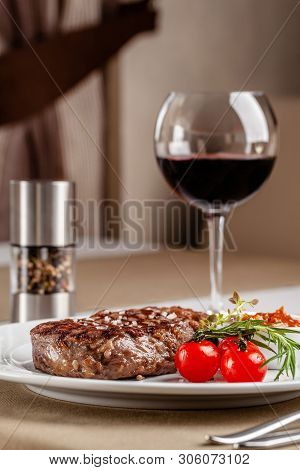 American Cuisine. Beef Steak With Red Bbq Tomato Sauce And Cherry Tomatoes. A Glass Of Cool Wine. Se