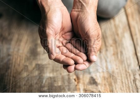 Male Beggar Hands Seeking Money, Coins From Human Kindness On The Wooden Floor At Public Path Way Or