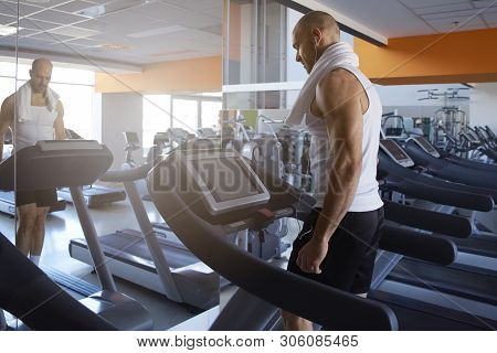 Sporty Man Is Working Out In Gym. Doing Cardio Training On Treadmill. Running On Treadmill.
