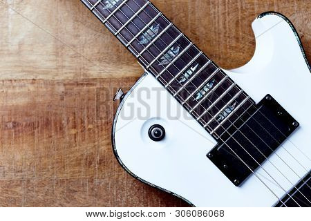Body And Fretboard Of Modern Electric Guitar On Rustic Wooden Background. Top View. Copy Space.