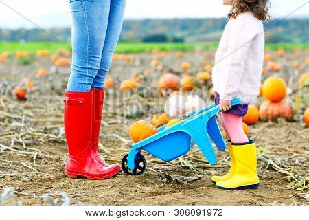 Legs Of Young Woman And Her Little Kid Girl Daugher In Rainboots. Woman In Red Gum Boots, Child In Y