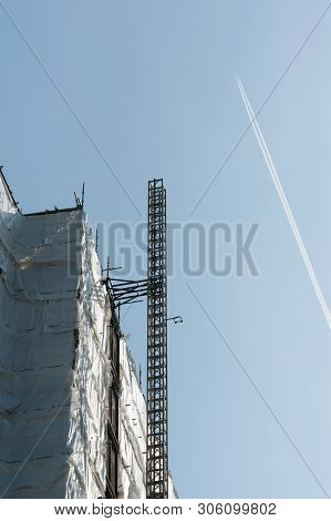 Tower Block Construction Elevator Rigging And Aircraft Contrails Against Blue Sky