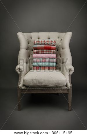 Armchair And A Plie Of Colourful Throws On Grey Background
