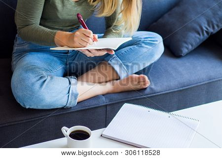 Woman Writing On Couch At Home