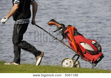 Golf player walks with golf clubs bag poster