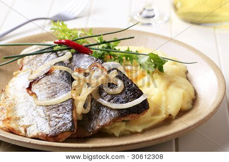 Two grilled trout fillets with mashed potatoes and herbs on a brown plate