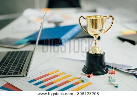 Champion Golden Trophy On Table.award Trophy On Working Table With Document And Contract