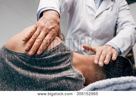 Chiropractor In White Coat Massaging Neck Of Man