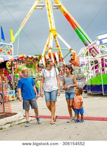 Candid photo of a smiling family group having fun at an outdoor carnival or theme park. Full length photo of People enjoying summer time outdoors at a fun destination