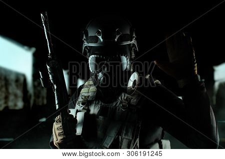 Photo Of A Fully Equipped Soldier In Black Armor Tactical Vest, Gas Mask, Automatic Rifle, Gloves An