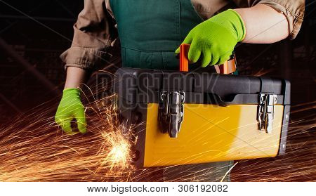 Photo Of A Worker In Green Overall Outfit With Protective Gloves Holding Yeallow Toolbox With Sparks