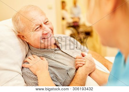 Happy senior man being cared for by nursing assistant at retirement home or at home