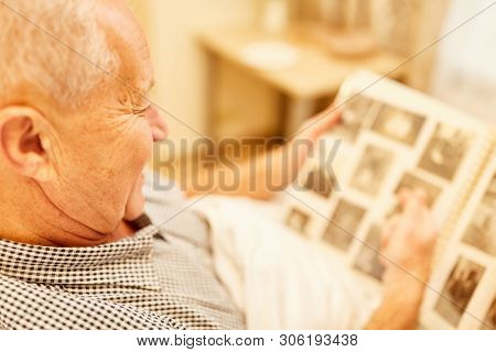 Old man with dementia or Alzheimer's in nursing home looks at a photo album