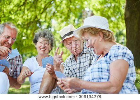Group seniors as retirees and friends have fun playing cards in the park