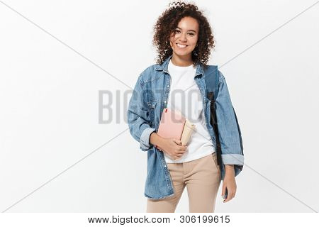 Portrait of a pretty cheerful casual african girl carrying backpack standing isolated over white background, holding textbooks