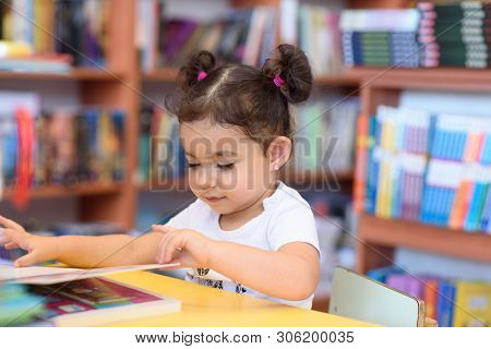Little Girl Indoors In Front Of Books. Cute Young Toddler Sitting On A Chair Near Table And Reading