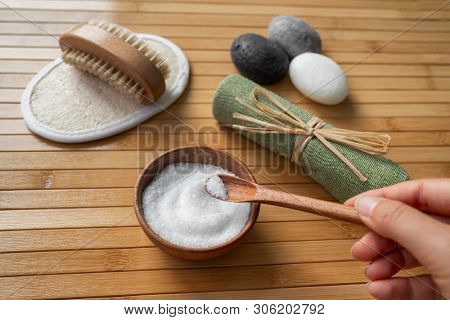 Wellness spa products woman holding bath epsom salts in natural wooden bowl for foot scrub skin body heatlh care. Scrubbing loofah pad, nail brush, exfoliation towel.
