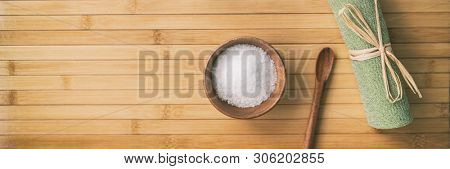 Bath salts spa wellness banner background. Top view of objects on bamboo texture. Exfoliation towel salt in wood bowl and spoon. Panoramic crop. poster