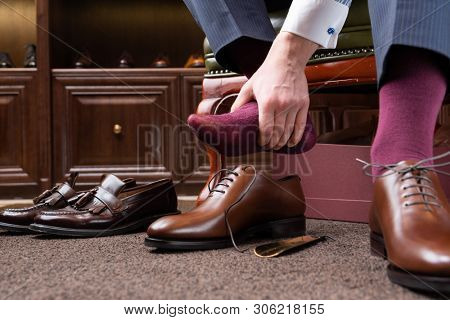 Trying new tight shoes. Man is putting on a new pair of luxury brown full grain leather shoes at footwear store and holding foot painfully. Old shoes left behind.