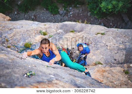 Athletic Beautiful Blonde Hair Woman Climbs A Rock In The Forest With Rope. Sport Climbing, Lead. Up