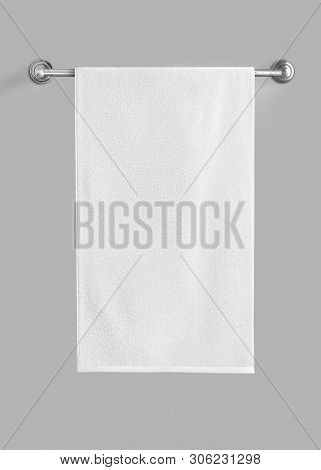 White Cotton Terry Towel Hanging On The Rail Isolated. White Towel Against The Gray Background.