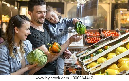 Happy Family Buys Vegetables. Cheerful Family Of Three Choosing Tomatoes In Vegetable Department Of