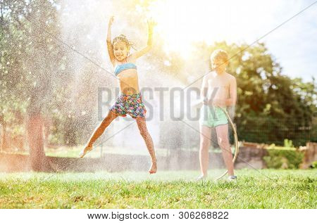 Happy Little Girl Jumps Under Water, When Brother Pours Her From Garden Hose. Hot Summer Days Activi